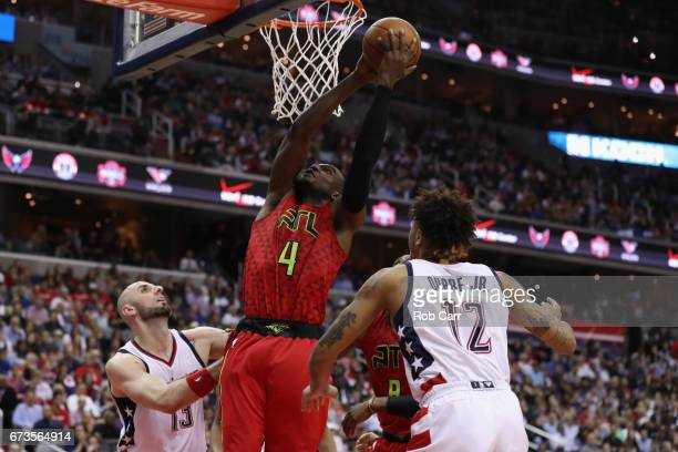 Paul Millsap of the Atlanta Hawks puts up a shot between Marcin Gortat and Kelly Oubre Jr #12 of the Washington Wizards in the second half in Game...