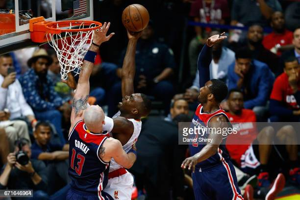 Paul Millsap of the Atlanta Hawks shoots a basket over Marcin Gortat and John Wall of the Washington Wizards during the third quarter in Game Three...