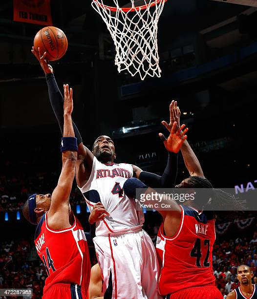Paul Millsap of the Atlanta Hawks shoots against Paul Pierce and Nene Hilario of the Washington Wizards during Game Two of the Eastern Conference...