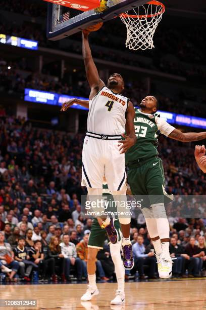Paul Millsap of the Denver Nuggets dunks against Sterling Brown of the Milwaukee Bucks at Pepsi Center on March 9 2020 in Denver Colorado NOTE TO...