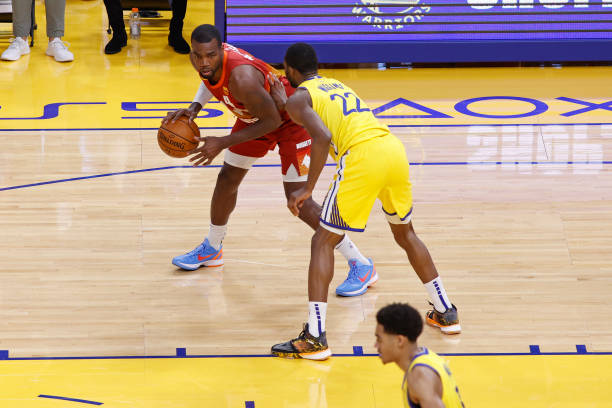 Paul Millsap of the Denver Nuggets handles the ball as Andrew Wiggins of the Golden State Warriors plays defense during the game on April 23, 2021 at...