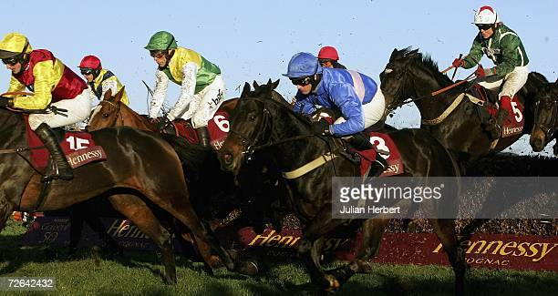 Paul Moloney and State of Play clear the 10th fence before landing The Hennessy Cognac Gold Cup Steeple Chase Race run at Newbury Racecourse on...
