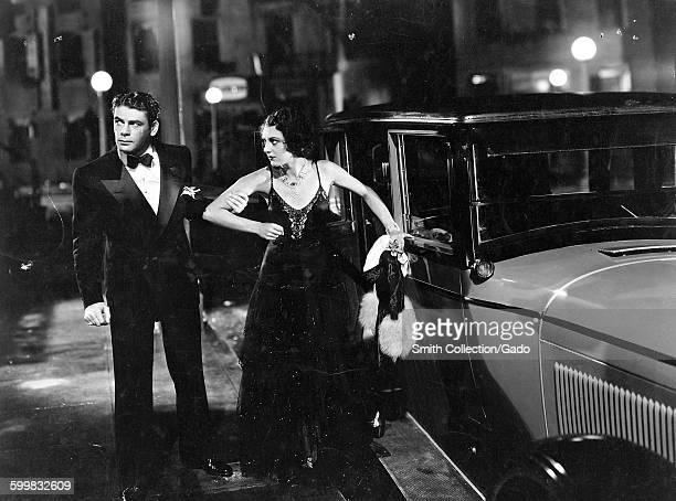Paul Muni and Ann Dvorak exiting a car Muni gripping Dvorak by the arm in a movie still from an unidentified film 1945
