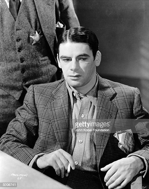 Paul Muni glowers menacingly in his role as ruthless gangster Tony Camonte in 'Scarface' directed by Richard Rosson and Howard Hawks A man stands...