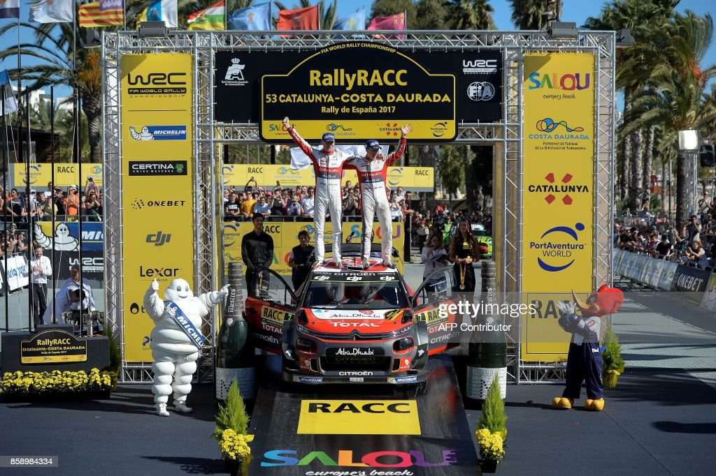 Paul Nagle of Ireland (L) and British Kris Meeke celebrate on the podium after winning the 53th Rally of Catalonia in Salou near Tarragona on October 8, 2017. Britain's Kris Meeke bagged his second win of the season at the Rally of Catalonia as France's Sebastian Ogier took a big step towards a fifth straight world title. / AFP PHOTO / Josep LAGO