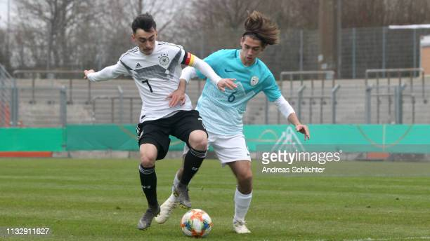 Paul Nebel of Germany U17 challenges Aleks Zlatkov of Slovenia U17 during the UEFA Elite Round match between Germany U17 and Slovenia U17 on March 26...