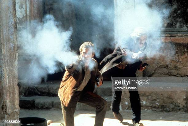 Paul Newman and Robert Redford firing guns in a scene from the film 'Butch Cassidy and the Sundance Kid' 1969