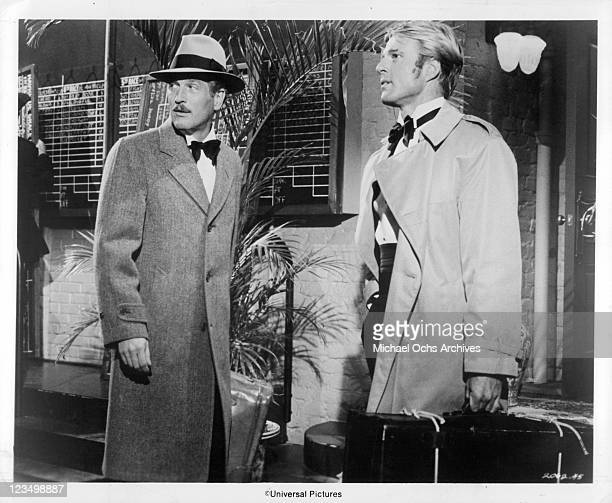 Paul Newman and Robert Redford stand in trench coats in a scene from the film 'The Sting' 1973
