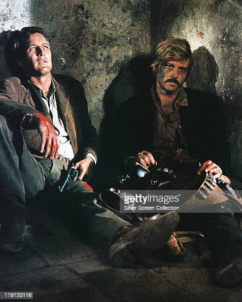 Paul Newman holding a handgun with his other hand covered in blood sitting alongside a despairing Robert Redford in a publicity still issued for the...