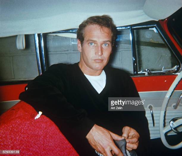 Paul Newman in the 1950's, sitting in a red car with white interior. The photograph was taken with a star flash camera. The photographer was walking...