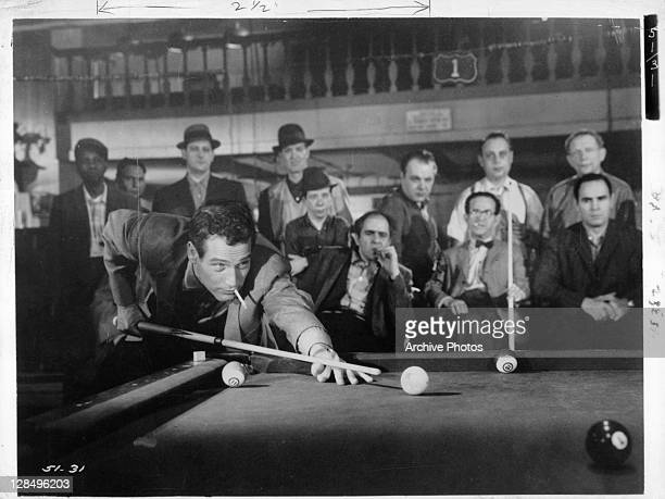 Paul Newman lets a lit cigarette hang from his mouth while lining up a pool shot in a scene from the film 'The Hustler' 1961