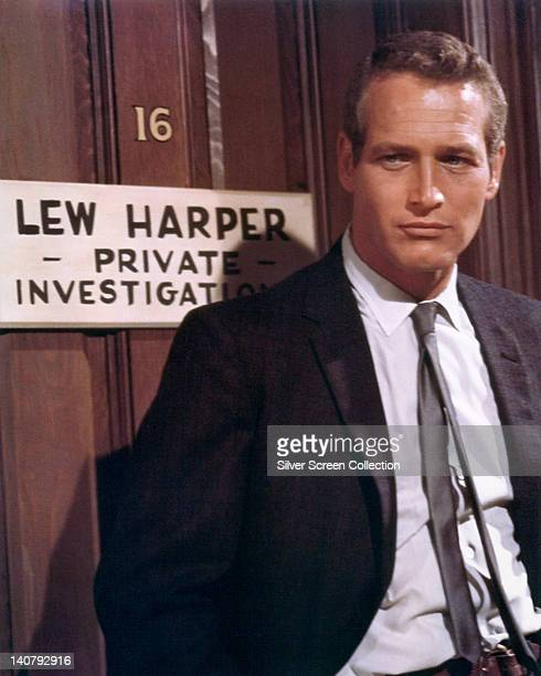 Paul Newman US actor wearing a black suit with a white shirt and a black tie posing in front of a door with the sign 'Lew Harper Private...