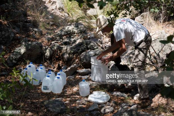 Paul Nixon a volunteer with Green ValleySahuarita Samaritans checks on food and water supplies at a water drop near Nogales Arizona on July 14 2019...