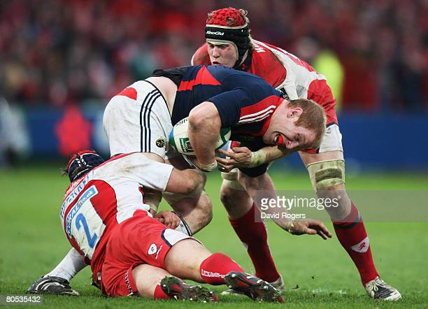Paul O'Connell of Munster is hauled down by Andy Titterrell and Luke Narraway of Gloucester during the Heineken Cup quarter final match between...