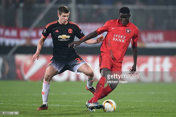 Paul Onuachu of FC Midtjylland and Paddy McNair of Manchester United compete for the ball during the UEFA Europa League round of 32 first leg match...