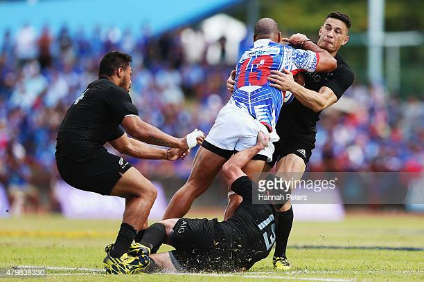 Paul Perez of Manu Samoa charges into Ryan Crotty of the New Zealand All Blacks and Sonny Bill Williams of the New Zealand All Blacks during the...