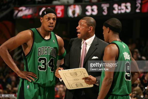 Paul Pierce and Rajon Rondo of the Boston Celtics listen to head coach Doc Rivers during a break in the action against the Cleveland Cavaliers in...