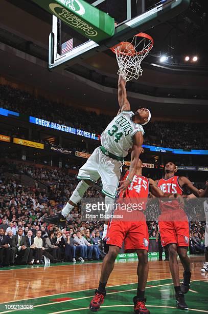 Paul Pierce of the Boston Celtics dunks against Derrick Favors of the New Jersey Nets on February 16 2011 at the TD Garden in Boston Massachusetts...