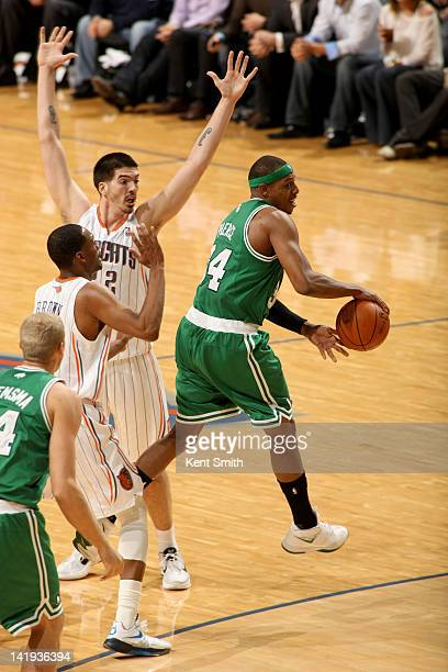 Paul Pierce of the Boston Celtics makes the pass behind his back against Byron Mullens and Derrick Brown of the Charlotte Bobcats at the Time Warner...
