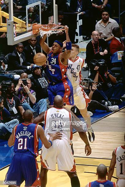 Paul Pierce of the Eastern Conference AllStars dunks against Andrei Kirilenko and Shaquille O'Neal of the Western Conference AllStars during the 2004...
