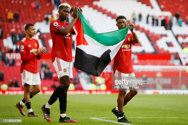 Paul Pogba and Amad Diallo of Manchester United applaud the fans whilst holding a Palestine flag after the Premier League match between Manchester...