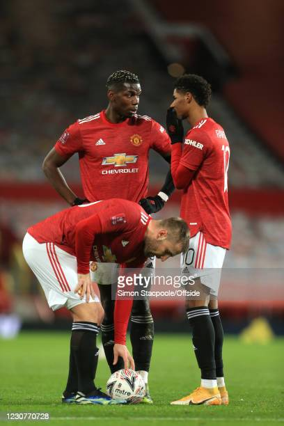 Paul Pogba and Marcus Rashford of Man Utd speak as Luke Shaw sets the ball during The Emirates FA Cup Fourth Round match between Manchester United...