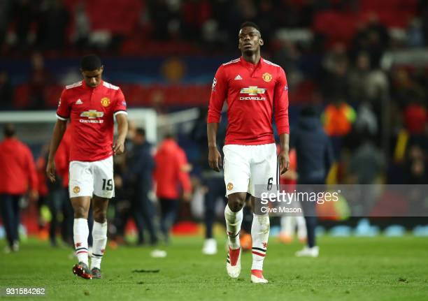 Paul Pogba and Marcus Rashford of Manchester United look dejected in defeat after the UEFA Champions League Round of 16 Second Leg match between...