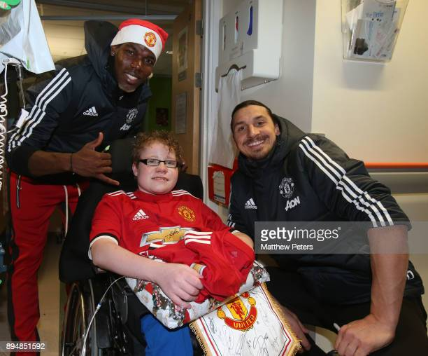 Paul Pogba and Zlatan Ibrahimovic of Manchester United deliver Christmas presents to Kayden during the club's annual Christmas hospital visits at...