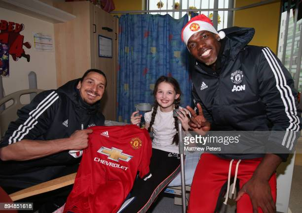 Paul Pogba and Zlatan Ibrahimovic of Manchester United deliver Christmas presents to Delilah during the club's annual Christmas hospital visits at...