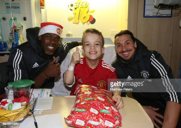 Paul Pogba and Zlatan Ibrahimovic of Manchester United deliver Christmas presents to Morgan during the club's annual Christmas hospital visits at...