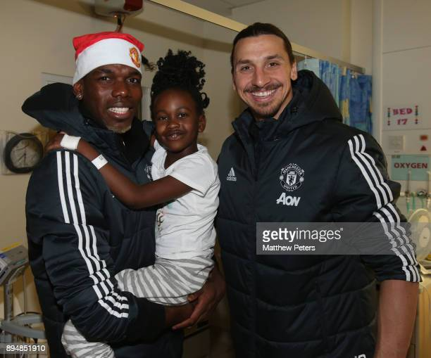 Paul Pogba and Zlatan Ibrahimovic of Manchester United deliver Christmas presents to Olivia during the club's annual Christmas hospital visits at...