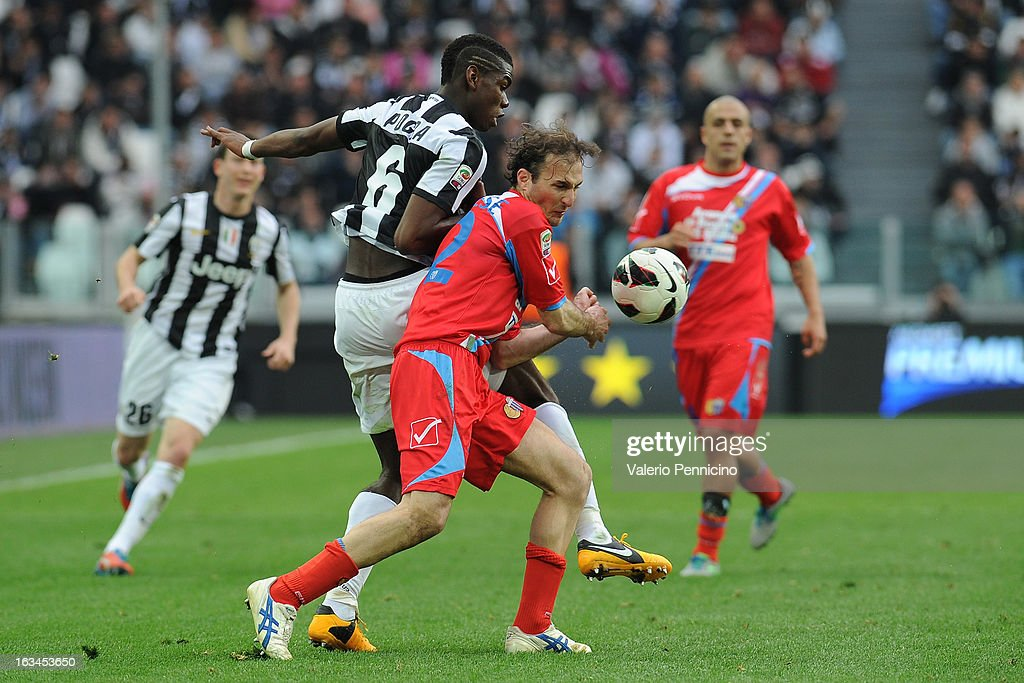 Paul Pogba (L) of FC Juventus competes with Giovanni Marchese of Calcio Catania during the Serie A match between FC Juventus and Calcio Catania at Juventus Arena on March 10, 2013 in Turin, Italy.