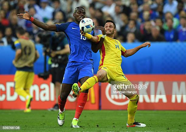 Paul Pogba of France and Florin Andone of Romania compete for the ball during the UEFA Euro 2016 Group A match between France and Romania at Stade de...