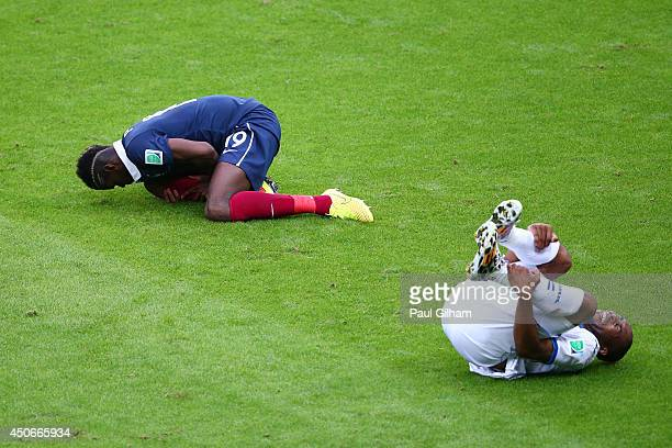 Paul Pogba of France and Wilson Palacios of Honduras lie on the floor after a challenge during the 2014 FIFA World Cup Brazil Group E match between...