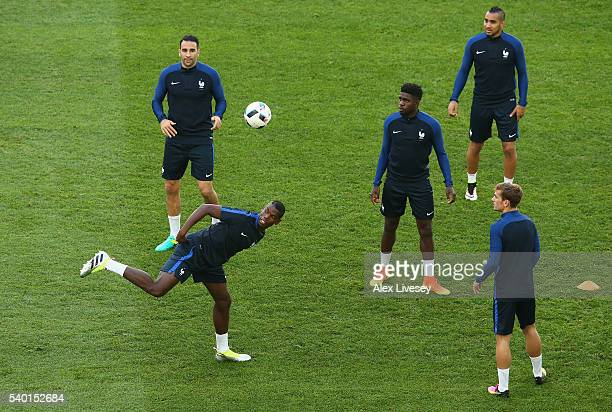 Paul Pogba of France controls the ball as team mates look on during a training session ahead the UEFA EURO 2016 Group A match between France and...