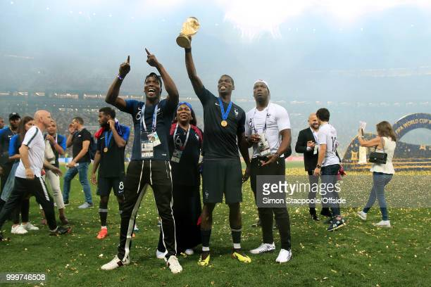Paul Pogba of France hold the trophy aloft alongside his mother Yeo and his brother Mathias and Florentin after the 2018 FIFA World Cup Russia Final...