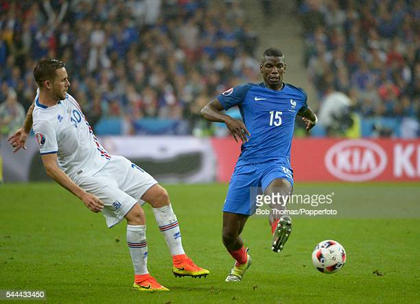 Paul Pogba of France is challenged by Gylfi Sigurdsson of Iceland during the UEFA EURO 2016 quarter final match between France and Iceland at Stade...