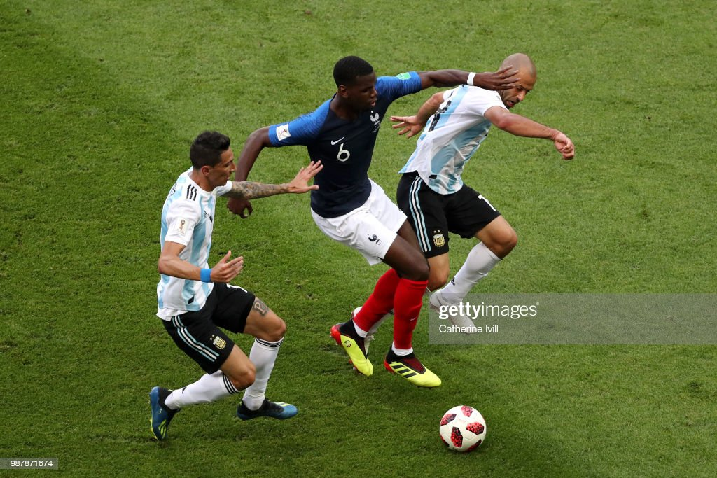 Paul Pogba of France is challenged by Javier Mascherano and Angel Di Maria of Argentina during the 2018 FIFA World Cup Russia Round of 16 match between France and Argentina at Kazan Arena on June 30, 2018 in Kazan, Russia.