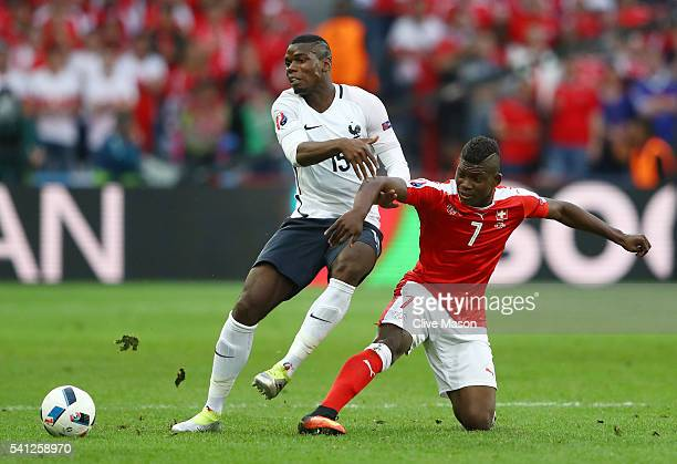 Paul Pogba of France is tackled by Breel Embolo of Switzerland during the UEFA EURO 2016 Group A match between Switzerland and France at Stade...