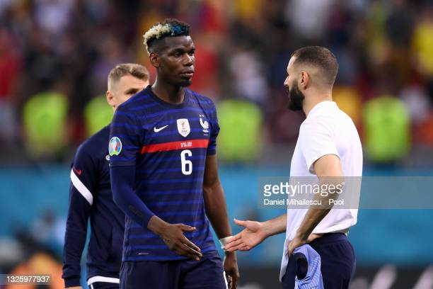 Paul Pogba of France looks dejected as he interacts with team mate Karim Benzema after the UEFA Euro 2020 Championship Round of 16 match between...