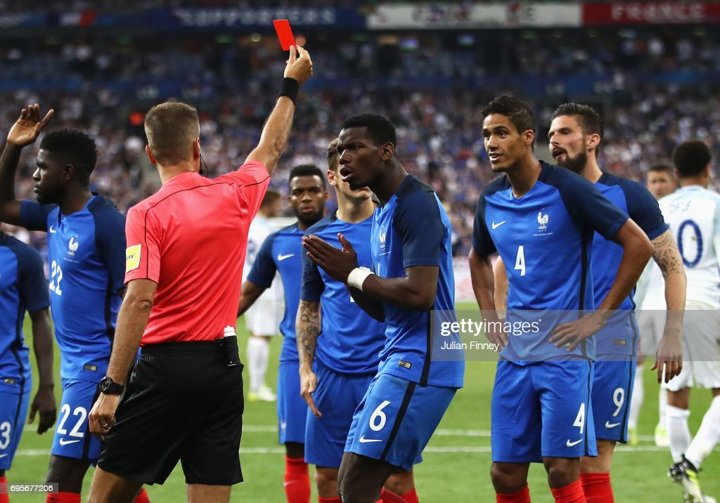 Paul Pogba of France (6) reacts as Raphael Varane of France (4) is shown a red card and is sent off by referee Davide Massa during the International Friendly match between France and England at Stade de France on June 13, 2017 in Paris, France.