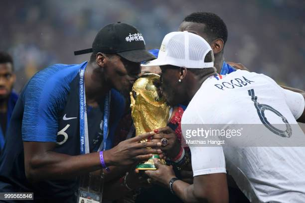 Paul Pogba of France's brother Florentin Pogba and Mathias Pogba celebrate with the World Cup Trophy following France's victory in the 2018 FIFA...