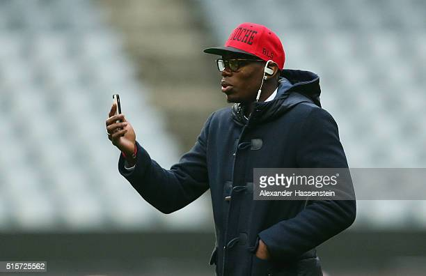 Paul Pogba of Juventus speaks on his mobile phone as he walks on the pitch prior to a Juventus press conference ahead of their UEFA Champions League...