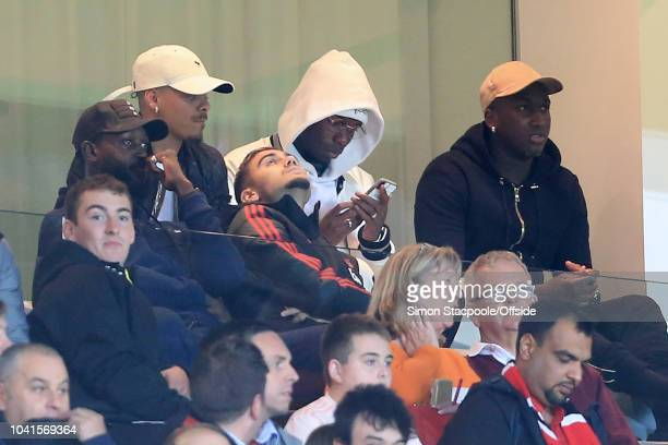 Paul Pogba of Man Utd looks at his mobile phone as he watches the game from a box behind teammate Andreas Pereira of Man Utd during the Carabao Cup...