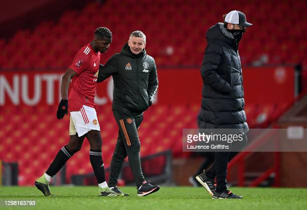 Paul Pogba of Manchester United and Ole Gunnar Solskjær, Manager of Manchester United interact as Jurgen Klopp, Manager of Liverpool makes their way...
