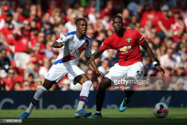Paul Pogba of Manchester United battles for possession with Wilfried Zaha of Crystal Palace during the Premier League match between Manchester United...