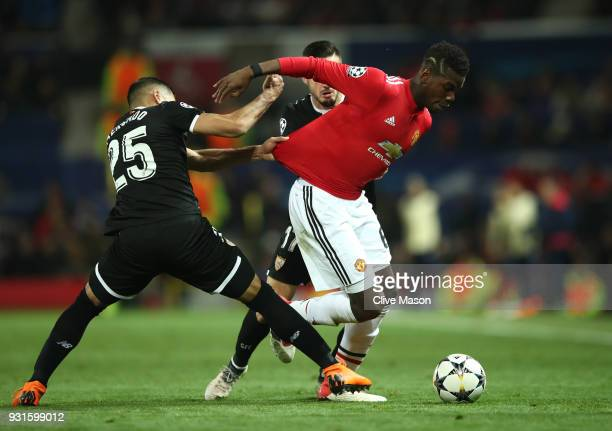 Paul Pogba of Manchester United battles with Gabriel Mercado and Pablo Sarabia of Sevilla during the UEFA Champions League Round of 16 Second Leg...