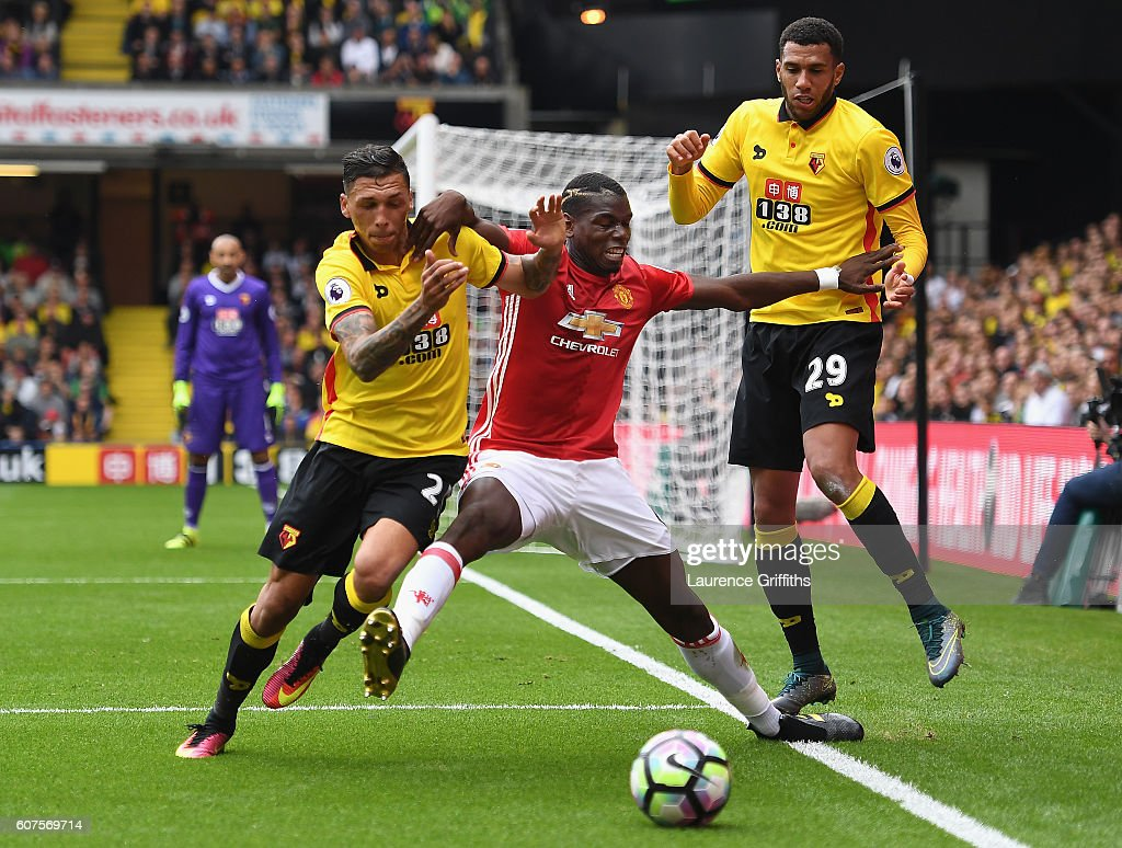 Paul Pogba of Manchester United battles with Jose Holebas and Etienne Capoue of Watford during the Premier League match between Watford and Manchester United at Vicarage Road on September 18, 2016 in Watford, England.