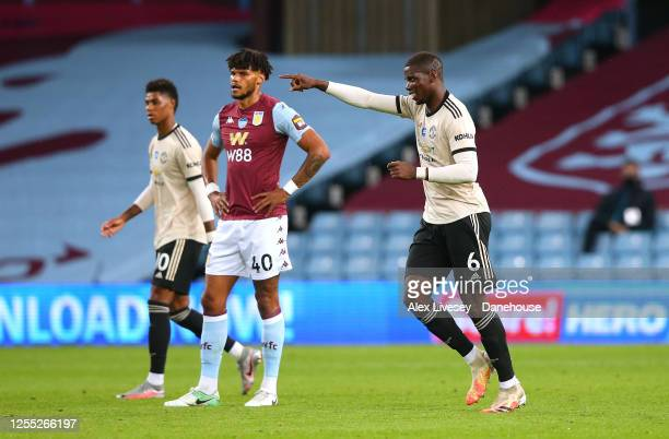 Paul Pogba of Manchester United celebrates after scoring their third goal as Tyrone Mings of Aston Villa looks on during the Premier League match...