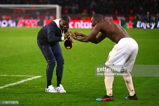Paul Pogba of Manchester United celebrates at fulltime with teammate Romelu Lukaku following the UEFA Champions League Round of 16 Second Leg match...